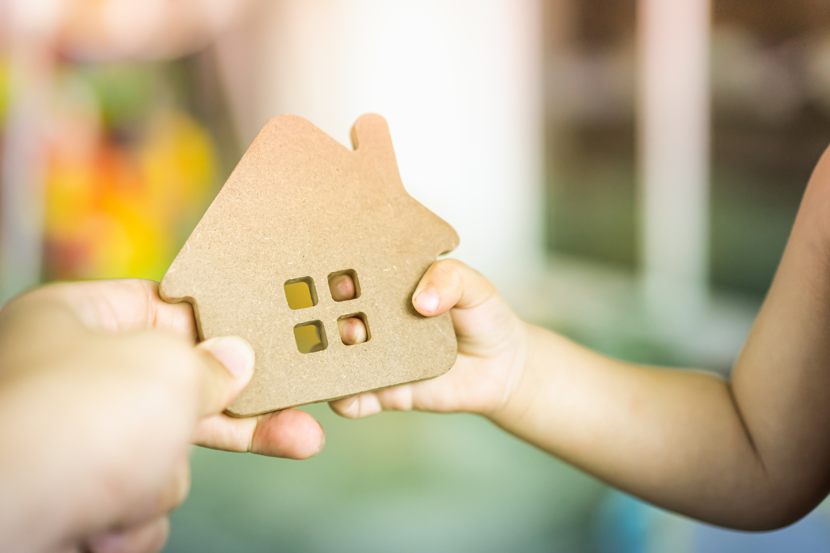 Baby Hands holding a house model with mother hand. The concept of relocation, mortgage, inheritance, family assurance protection and legacy planning.
